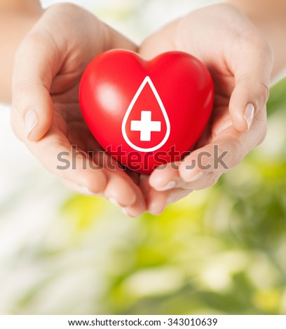 healthcare, medicine and blood donation concept - female hands holding red heart with donor sign over green natural background - stock photo