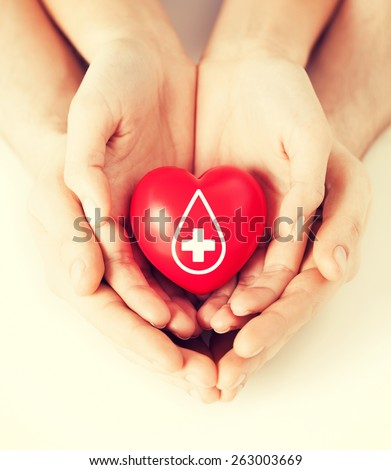 healthcare, medicine and blood donation concept - male and female hands holding red heart with donor sign - stock photo