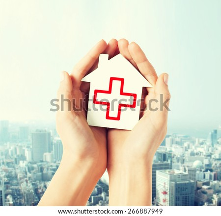 healthcare, medicine and charity concept - hands holding white paper house with red cross sign - stock photo