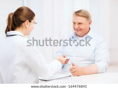 healthcare, medicine and elderly concept - female doctor or nurse with old man giving prescription