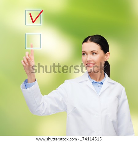 healthcare, medicine and technology concept - smiling female doctor pointing to checkbox - stock photo