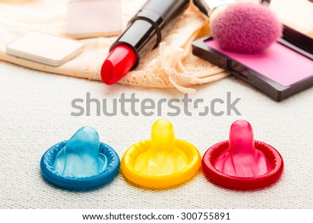 Healthcare medicine, contraception and birth control. Closeup colorful condoms and cosmetics on lace lingerie. - stock photo