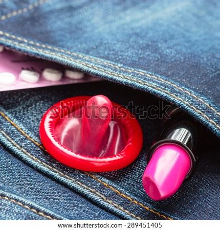 Healthcare medicine, contraception and birth control. Closeup oral contraceptive pills, condom and pink lipstick in denim pocket. - stock photo