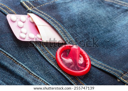 Healthcare medicine, contraception and birth control. Closeup oral contraceptive pills, red condom on denim pocket background - stock photo