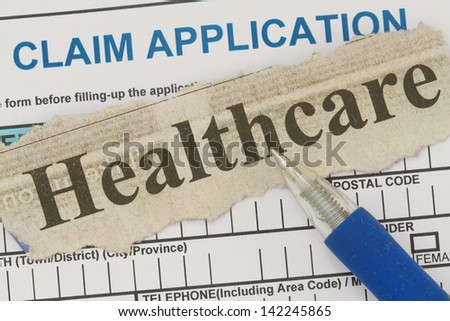 Healthcare newspaper cutout with blank worker's claim form. - stock photo