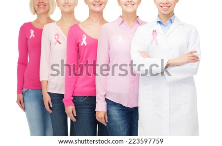 healthcare, people and medicine concept - close up of smiling women in blank shirts with pink breast cancer awareness ribbons over white background - stock photo