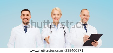 healthcare, people and medicine concept - group of doctors with stethoscope and clipboard making handshake gesture over blue background - stock photo