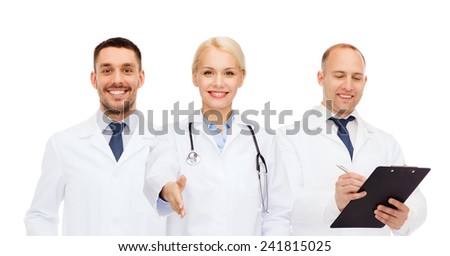 healthcare, people and medicine concept - group of doctors with stethoscope and clipboard making handshake gesture - stock photo