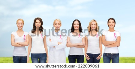healthcare, people and medicine concept - group of smiling women in blank t-shirts with pink breast cancer awareness ribbons blue sky and grass background