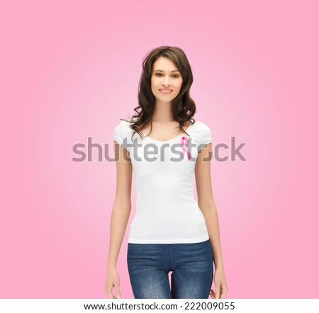 healthcare, people, charity and medicine concept - smiling young woman in t-shirt with breast cancer awareness ribbon over pink background - stock photo