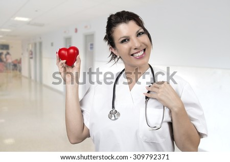 healthcare, people, charity and medicine concept -young smiling doctor with small red heart