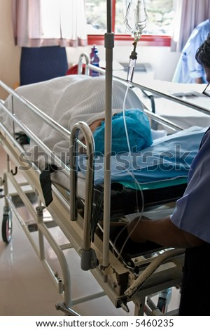 Healthcare personnel carry one patient after surgery in the recovery room - stock photo