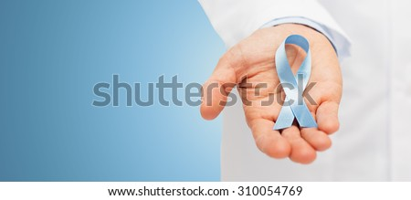 healthcare, profession, people and medicine concept - close up of male doctor hand holding sky blue prostate cancer awareness ribbon over blue background - stock photo