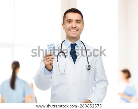 healthcare, profession, people and medicine concept - smiling male doctor in white coat with tablets over group of medics at hospital background - stock photo