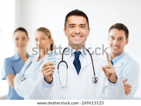 healthcare, profession, people and medicine concept - smiling male doctor in white coat with tablets pointing his finger up over group of medics at hospital background - stock photo