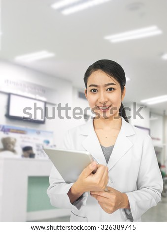 healthcare, profession, stomatology and medicine concept:smiling woman young aged doctor hand holding blur tablet shows a list of patients. over blur medical office background - stock photo