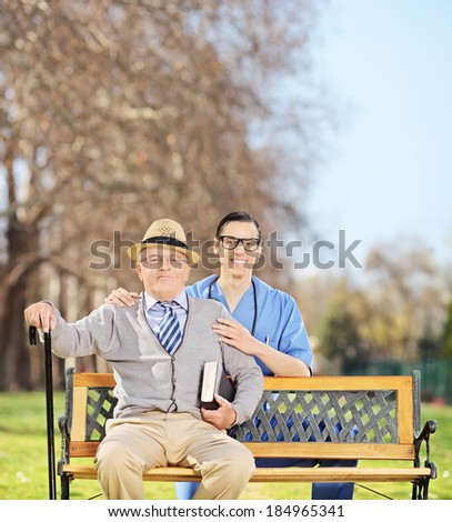Healthcare professional and a senior posing on a bench in park shot with tilt and shift lens - stock photo