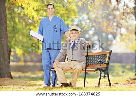 Healthcare professional in uniform standing next to a senior man seated on wooden bench in a yard - stock photo