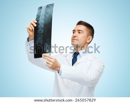 healthcare, roentgen, people and medicine concept - male doctor in white coat looking at x-ray over blue background - stock photo