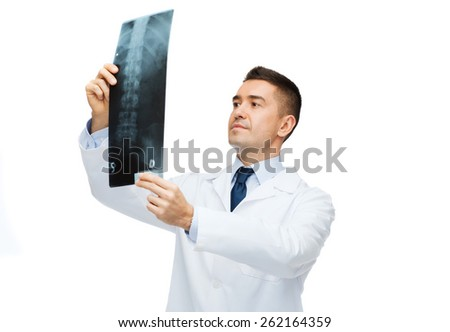 healthcare, rontgen, people and medicine concept - male doctor in white coat looking at x-ray - stock photo