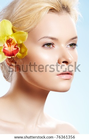 Healthcare, spa, wellness, beauty and skincare. Close-up portrait of beautiful woman with natural make-up, perfect shiny skin, yellow flower in her hair on blue sky background