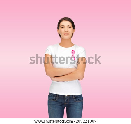 healthcare, support, people and medicine concept - smiling woman in blank white t-shirt with breast cancer awareness ribbon over pink background