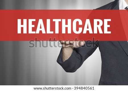 Healthcare word on virtual screen touch by business man at red tab - stock photo