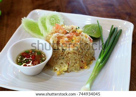 Healthly foods Fried Rice with Shrimp and some vegetables with Chilli and fish sauce in white plate on wooden background, Thai foods concept.