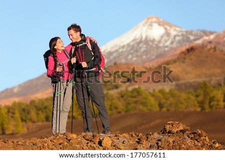 Healthy active lifestyle. Hiker people hiking in beautiful mountain nature landscape. Woman and man hikers laughing resting taking break during hike on volcano Teide, Tenerife, Canary Islands, Spain. - stock photo