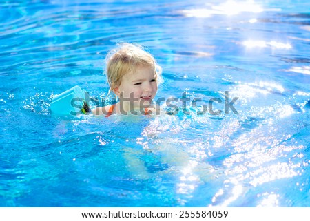 Healthy active little child, laughing blonde toddler girl swimming in outdoors pool on beautiful sunny day learning to float using armbands  - stock photo