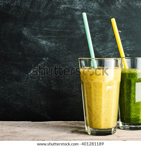 Healthy almond and banana and colorful green cole, or fresh kale, smoothies served in tall glasses for a tasty drink on a rustic table, slate background with copy space - stock photo