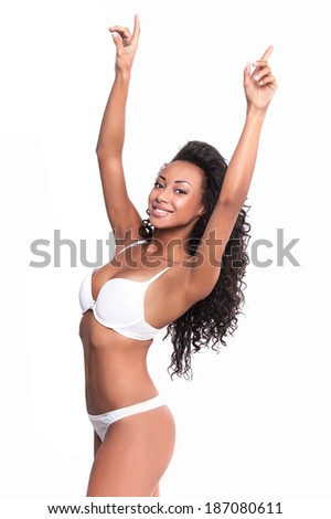 Healthy and beautiful. Attractive young Afro-American woman in white bra and panties posing against white background - stock photo