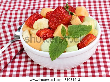 Healthy and delicious fresh fruit salad in a bowl garnished with mint leaves. - stock photo