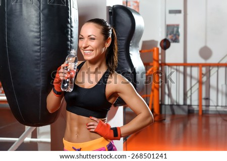 Healthy and fit. Young cheerful woman drinking water in a boxing gym and contagiously laughing - stock photo