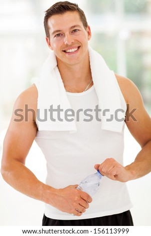 healthy and fit young man with water bottle in gym - stock photo