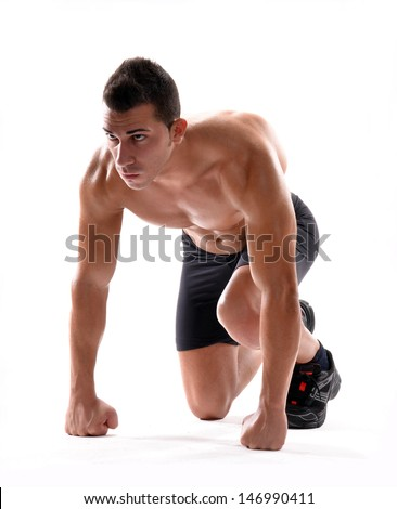 Healthy and fitness man on running start position on white background.