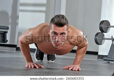 Healthy and fitness man training push ups exercise in a gym. - stock photo