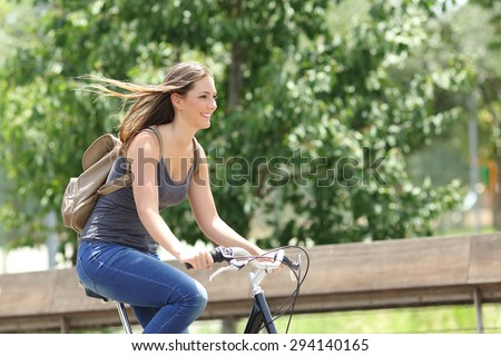 Healthy and happy cyclist woman riding fast a bicycle in a park - stock photo