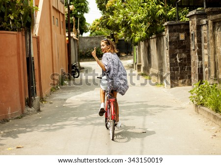 Healthy and happy cyclist woman riding fast a bicycle in a park.cute amazing smiling girl,floral dress summer vintage style,street evening sunlight.fashionable sunglasses,trendy street style.Bali boho - stock photo