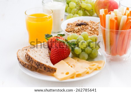 healthy and nutritious breakfast with fresh fruits and vegetables on white table, close-up, horizontal - stock photo