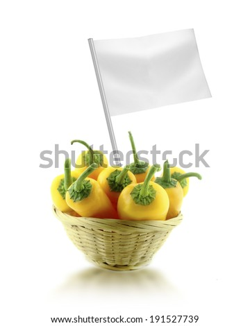 Healthy and organic food concept. Fresh Yellow chili pepper in straw dish with flag showing the benefits or the price of fruits. - stock photo