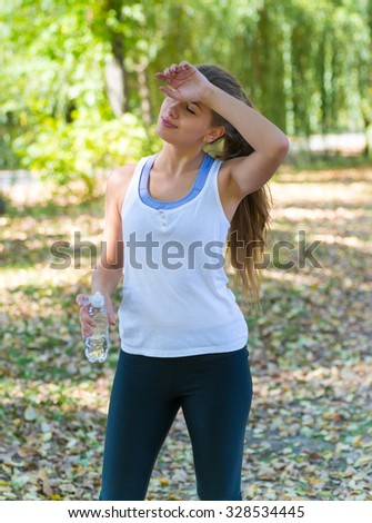 Healthy and Sporty Young Woman Drinking Water from the bottle. Doing Sport Outdoor. - stock photo