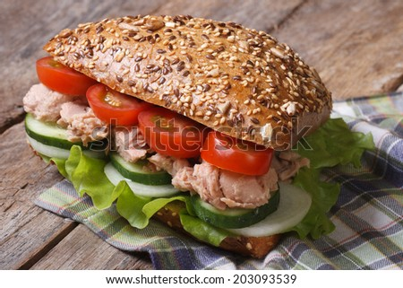 Healthy and tasty sandwich with tuna and vegetables closeup on old table. horizontal  - stock photo