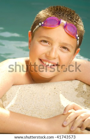 Healthy and upbeat young kid in the pool - stock photo