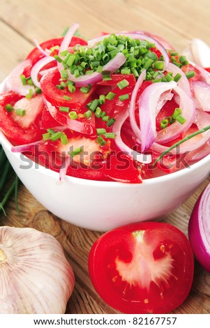 healthy appetizer : fresh tomato salad in white bowl with bunch of chives and raw tomatoes on twig , violet onion, garlic over wooden table - stock photo