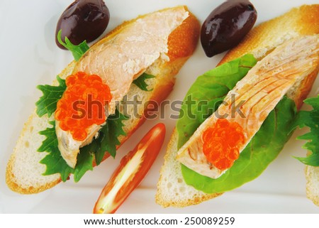 healthy appetizer : sandwich with sea salmon and red caviar, olives, tomato and lemon on white china plate isolated over white background