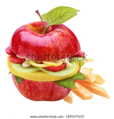 Healthy apple burger or sandwich with a farm fresh ripe red apple halved and filled with sliced tropical fruit including strawberry and kiwifruit and served with fruit batons or chips - stock photo