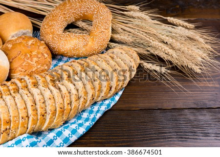 Healthy array of wheat products with assorted wholegrain, seed bread and crusty rolls with ripe ears of wheat and copy space - stock photo