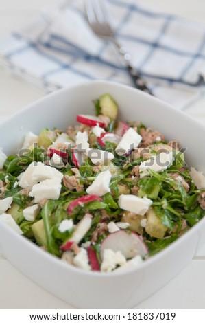 Healthy arugula salad with tuna and feta cheese - stock photo