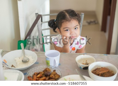 Healthy Asian child is eating.She is thinking about meal on the table and make decision to eat or not.